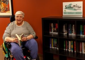 A woman in a motorized wheelchair smiles holding a book while sitting next to a bookcase of books.