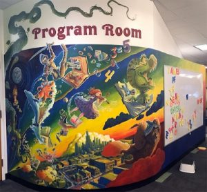 A painted mural on the wall of the library's Youth Services Room features storybook characters bursting out of books on a brightly colored background.